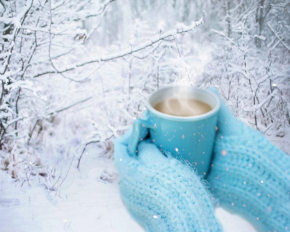 Vantklädd dricker kaffe i snöklädd skog