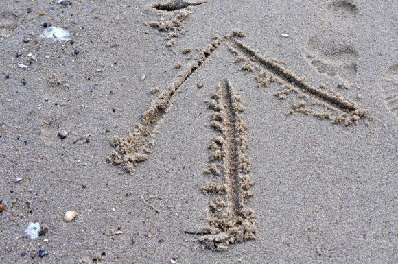Pil i sand som pekar uppåt och framåt