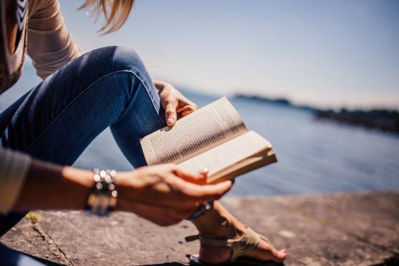 Kvinna läser bok vid havet